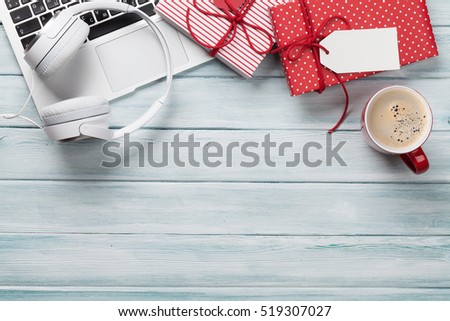 Christmas gift boxes, laptop, headphones and coffee cup on wooden background. Top view with copy space for your text