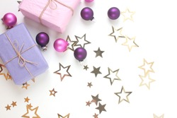 Christmas gift boxes with golden stars, pink and purple decorations on white background. Christmas border. Flat lay. Copy space.