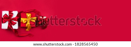 Christmas gift boxes with red and gold ribbons on a red banner background. Christmas and new year banner. Flat lay, top view, copy space, banner