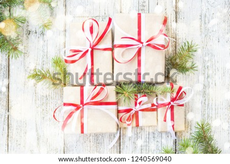 christmas gift boxes with red and white ribbon on wooden background with fir branches decorated with