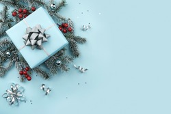 Christmas gift boxes with silver ribbons, decoration, bows, sparkles, fir branches, confetti on blue background. Xmas and New Year greeting card, winter holiday. Top view, banner