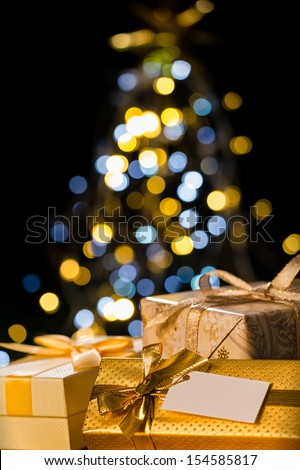 Christmas gift gold ribbon with a christmas tree in the background - stock photo