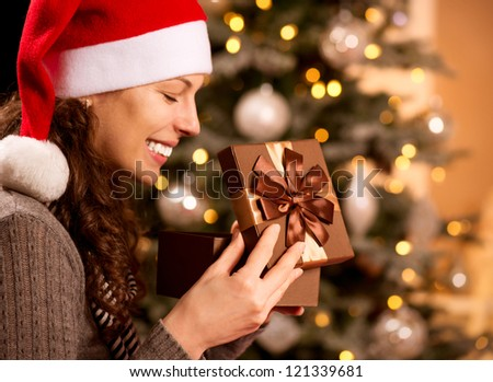 Christmas Gift.Happy Surprised Woman opening Gift box at home. Christmas Tree