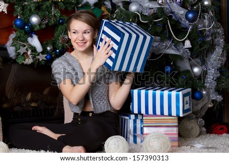 Christmas Gift.Happy Surprised Woman with Gift box at home. Christmas Tree