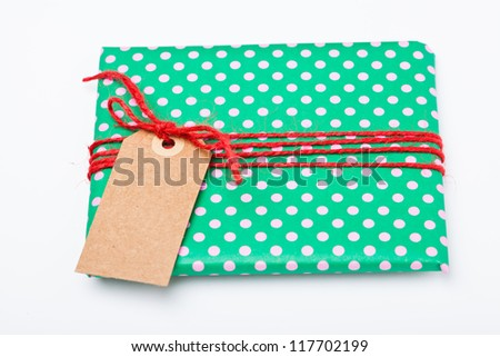 Christmas gift in green wrapping with dots, red string and brown cardboard tag