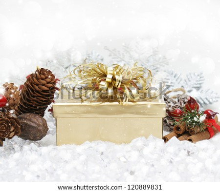 Christmas gift nestled in snow with pine cones and cinammon