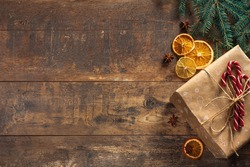 Christmas gift on wooden background. Frame from decorated Christmas tree on rustic wooden background with copy space for text. Happy New Year concept. Christmas mock-up or greeting card. Top view