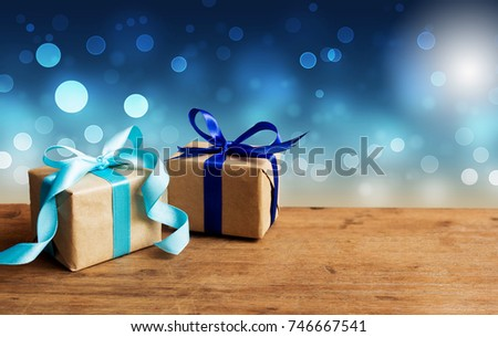 Christmas gift or New Year with blue ribbon on rustic wood table on night blue bokeh background. Tiny handmade gift concept.