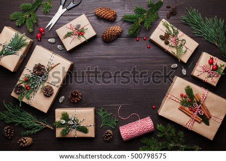 Christmas gift or present box wrapped in kraft paper with decoration on rustic wooden background from above. Flat lay style. #500798575