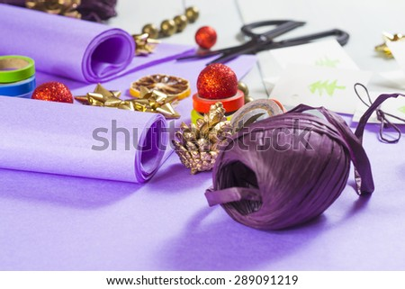 christmas gift packaging with purple papers and cards with christmas tree print
