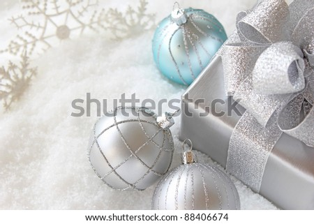 Christmas gift with balls in snow