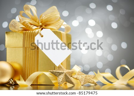 christmas gift with blank tag against bokeh lights background