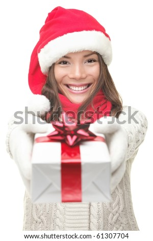 Christmas gift woman smiling holding present isolated on white background. Santa girl in winter sweater showing gift wearing Santa hat. Cute, beautiful model: mixed Asian / Caucasian.