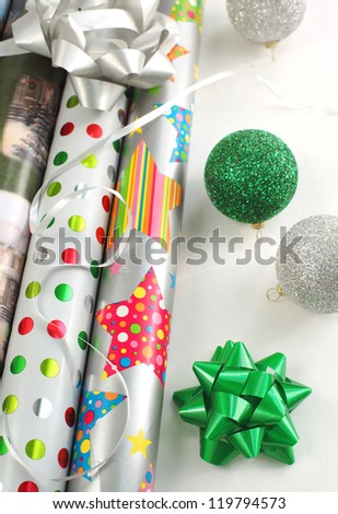 Christmas gift wrapping papers with ribbon and supplies.