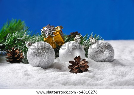 Christmas  gifts and balls on snow against blue background