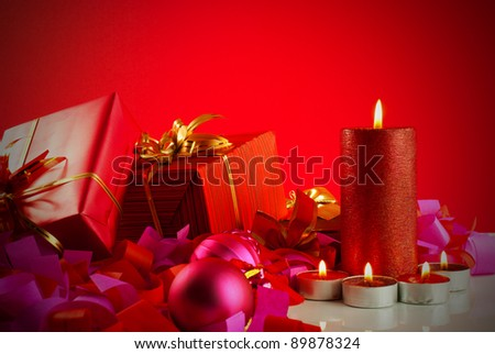 Christmas gifts and candles over red background