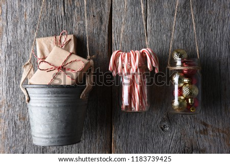 Christmas Gifts and Ornaments against a rustic wood wal. Items are in a metal pail and glass jars.
