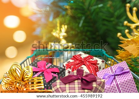 christmas gifts and presents in shopping trolley with christmas decorations and blurred lights on christmas tree