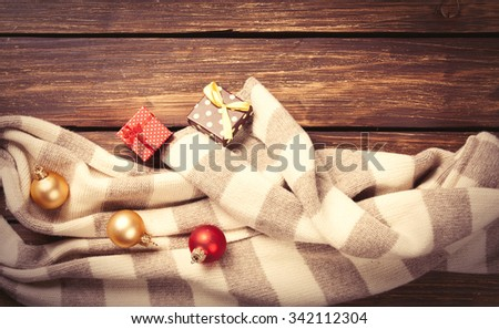 Christmas gifts and scarf on wooden background #342112304