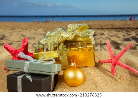 christmas gifts and  starfish on beach  with golden sand