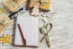 Christmas gifts, Christmas ornaments, candy and an open blank notebook on a light wooden table
