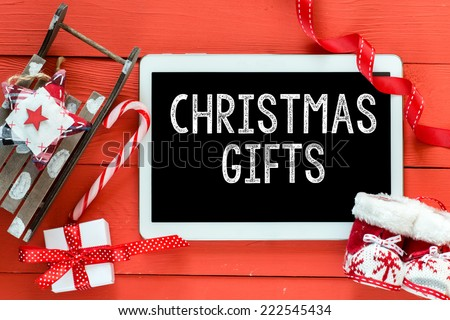 Christmas gifts inscription on white tablet on red wooden table. Sled and boots