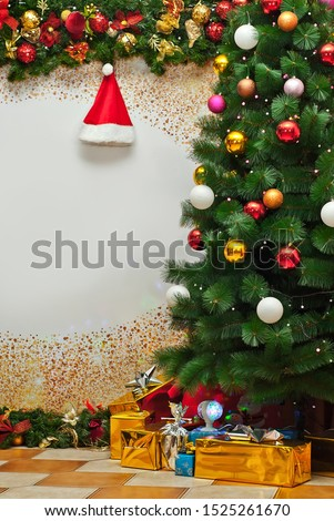 Christmas gifts near the Christmas tree. Holiday photo zone with decorations and decor. Part of the room is hung with Santa Claus garlands and hats. Free space for text on paper background. #1525261670