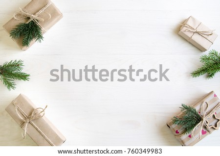 Christmas gifts on a white wooden background with sprigs of spruce. New Year gifts - Shutterstock ID 760349983