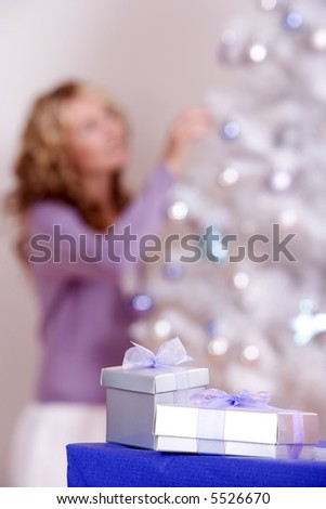 Christmas gifts ready for under the tree, with a woman hanging ornaments on the tree behind