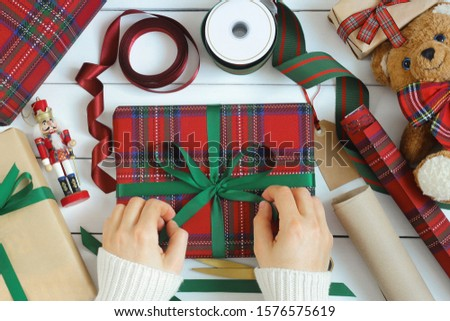 Christmas gifts wrapping, preparation for holiday, xmas concept. Female hands wrapping and decorating presents. Packed presents, ribbons, paper rolls and toys on white wooden table.  Top view.
