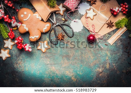 Christmas gifts wrapping with gingerbread man, star cookies, shears and handmade cardboard boxes on vintage background, top view, border #518983729