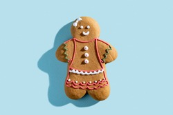 Christmas gingerbread bakery. Festive cookies. Traditional homemade culinary. Happy smiling biscuit decorated white icing ornament woman isolated on blue pastel.