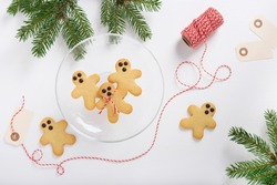 Christmas gingerbread butter cookies on glass plate, fir branches and striped decorative rope on the white wooden table. Top view.