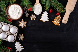 Christmas gingerbread cookies and ingredients for cooking on a black table top view. Christmas background with space for text.