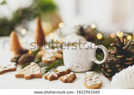 Christmas gingerbread cookies, coffee in stylish white cup, pine cones  and warm lights on white wooden table. Hello winter, cozy moody image with selective focus