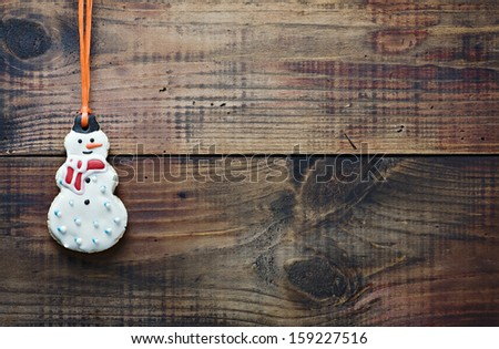 christmas gingerbread cookies hanging over wooden background