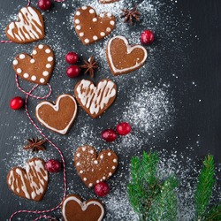 Christmas gingerbread cookies with festive decoration on black stone background, top view. Holiday concept.