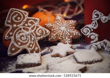 Christmas gingerbread cookies with flour,  festoon lights on purple background #528923671