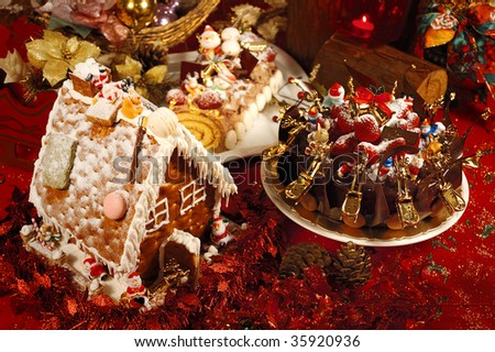 Christmas Gingerbread Houses and chocolate cake. Gingerbread house with lights inside, red background.
