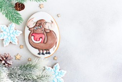 Christmas gingerbread in glaze in the form of a bull, Christmas symbols, on a white table with New Year's decor, horizontal, copy space