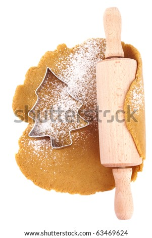 christmas gingerbread tree cookie cutter on dough with rolling pin, isolated on white