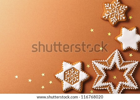 Christmas gingerbreads with golden stars on brown paper background. Top view