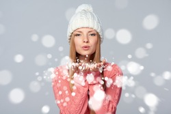 Christmas Girl. Beautiful caucasian woman wearing winter clothing hat blowing snow at you, looking at camera, over gray background