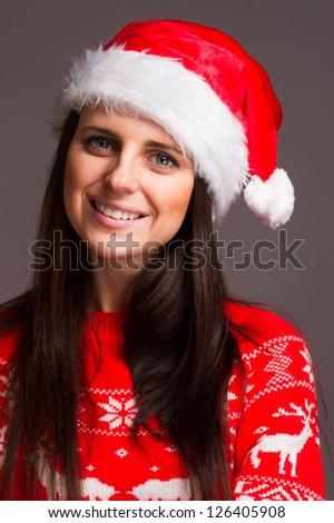 Christmas girl in red sweater over dark background. Studio shot.