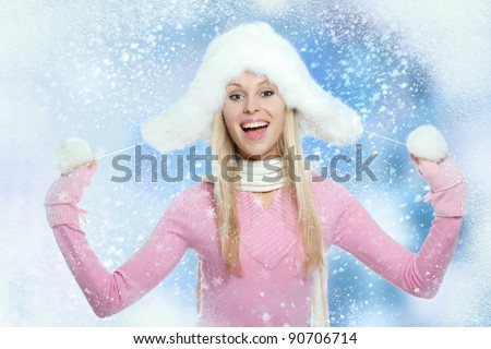 Christmas Girl. Winter new year woman, excited happy smile, wear warm fur hat scarf gloves holding snow in hands, over abstract christmas ornament with blowing snow flake background