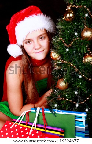 christmas girl with present bags over dark background
