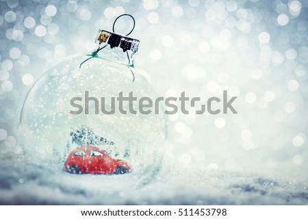 Stock Photo Christmas glass ball in snow with miniature winter world inside - car with Christmas tree, mountains. Glitter background.