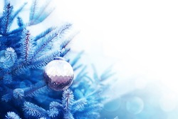 Christmas glass ball on a Christmas tree branch, closeup, soft selective focus. Blue christmas background with ball, copy space