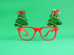 Christmas glasses decoration with Christmas tree and red ribbon on green background