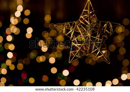 Christmas gold star against background of blurred lights